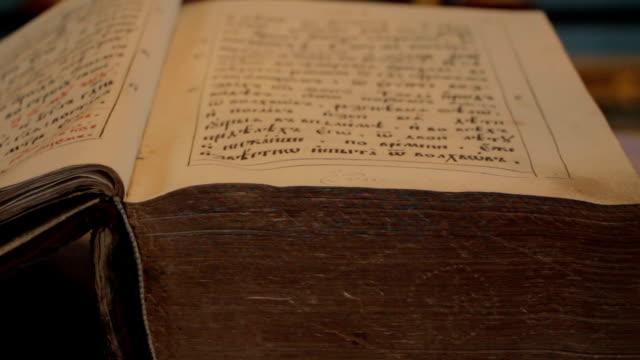 stockvideo's en b-roll-footage met een oude open kerk boek-close-up - heilig geschrift