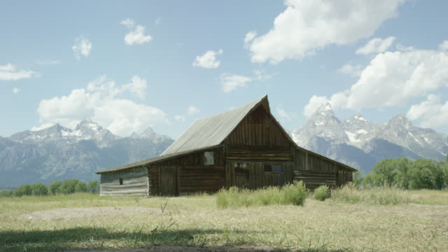 An Old Wooden Cabin/Barn Sits at the Base of the Grand Teton Mountains in Grand Teton National Park in Western Wyoming on a Sunny Day