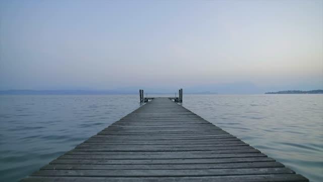 en gammal träbrygga sträcker sig in i det klarblå vattnet i sjön. en ensam stig mot naturens lugna och fridfulla tystnad, med vågornas ljuva ljud. - solar panel bildbanksvideor och videomaterial från bakom kulisserna