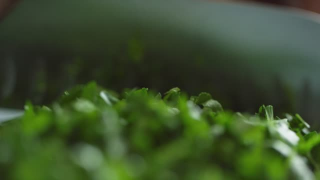 vídeos y material grabado en eventos de stock de una mujer caucásica más vieja chuta cilantro en una tabla de cortar con un cuchillo de cocina - cortar en trozos preparar comida