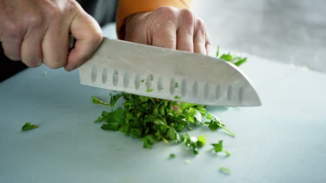 An Older Caucasian Woman Chops Cilantro on a Cutting Board with a Kitchen Knife