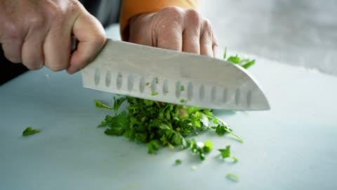 vídeos y material grabado en eventos de stock de una mujer caucásica más vieja chuta cilantro en una tabla de cortar con un cuchillo de cocina - cortar