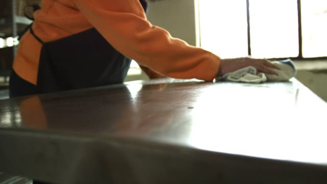 an older caucasian woman cleans a stainless steel countertop in a commercial kitchen with a dish cloth - acciaio inossidabile video stock e b–roll