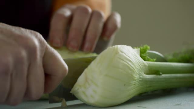 stockvideo's en b-roll-footage met een oudere kaukasische vrouw pikt venkel uit een metalen kom gevuld met groenten en plakjes het op een snijplank met een keuken mes - venkel
