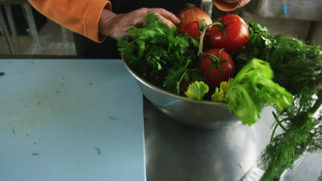 An Older Caucasian Woman Picks Vegetables Up off a Cutting Board and Places Them in a Metal Bowl in a Commercial Kitchen