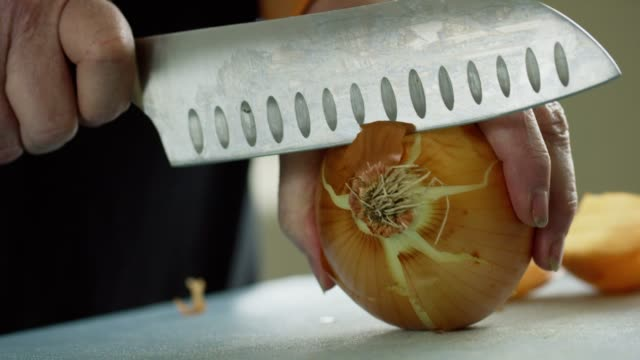 An Older Caucasian Woman Slices an Onion on a Cutting Board with a Kitchen Knife