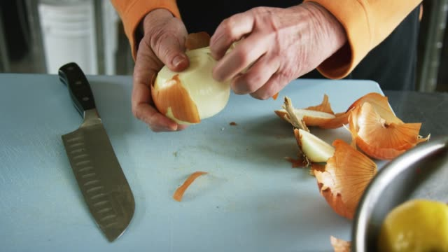 An Older Caucasian Woman Slices an Onion on a Cutting Board with a Kitchen Knife and Removes Its Outer Skin in a Commercial Kitchen