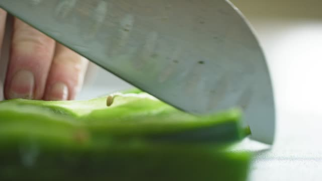 An Older Caucasian Woman Slices and Chops a Poblano Pepper on a Cutting Board with a Kitchen Knife