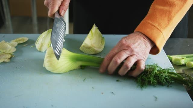 stockvideo's en b-roll-footage met een oudere kaukasische vrouw plakjes venkel op een snijplank met een keuken mes in een commerciële keuken - venkel