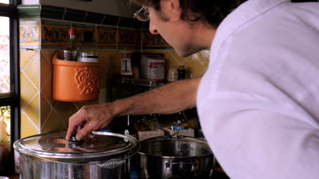 vídeos y material grabado en eventos de stock de un padre mayor y su hijo mirando dentro de una olla de comida que están preparando - pascua judía