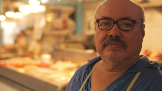 An older hispanic man with a mustache looks at the camera while standing in front of a fish market video
