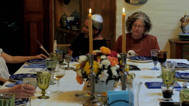 vídeos y material grabado en eventos de stock de un hombre mayor lee de la haggadah en una pascua seder- dolly - pascua judía