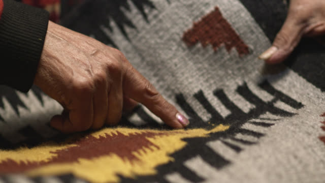 An Older Native American (Navajo) Woman's Hand's Point to Designs on a Navajo Blanket while a Younger Girl Watches