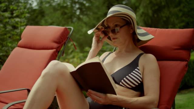 eine ältere frau am pool lesen sieht etwas und aufsteht, in zeitlupe - sun chair stock-videos und b-roll-filmmaterial
