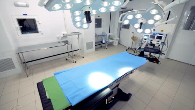ett operationsbord och kirurgiska ljus i ett rum. - ultra high definition television bildbanksvideor och videomaterial från bakom kulisserna