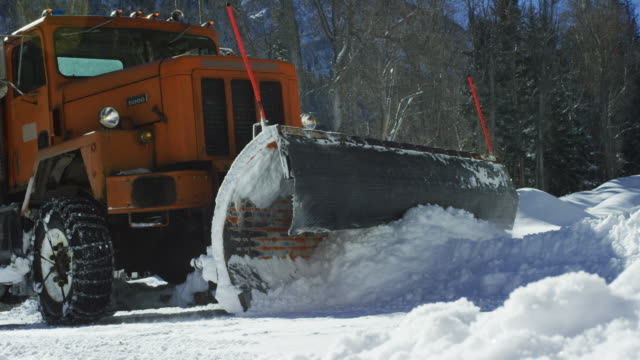 An Orange Tractor Plows Deep Snow Before Disappearing Behind a Snowdrift Next to a Forest in the Mountains in Winter on a Sunny Day An Orange Tractor Plows Deep Snow Before Disappearing Behind a Snowdrift Next to a Forest in the Mountains in Winter on a Sunny Day plow stock videos & royalty-free footage