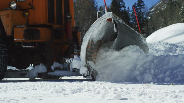 An Orange Tractor Plows Deep Snow Next to a Forest in the Mountains in Winter on a Sunny Day