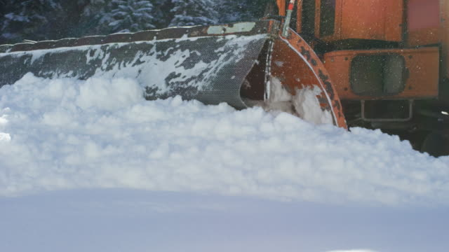 An Orange Tractor Plows Deep Snow Next to a Forest in Winter An Orange Tractor Plows Deep Snow Next to a Forest in Winter plow stock videos & royalty-free footage