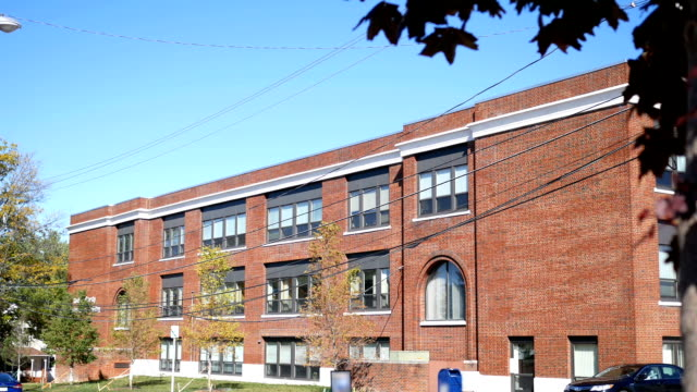 An outdoor afternoon establishing shot of a red brick school building in early fall video