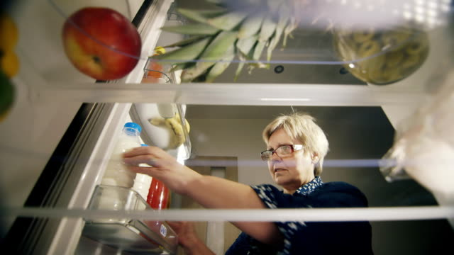 An senior woman Takes a bottle of milk from the refrigerator, checks the shelf life of the product. Healthy Eating video