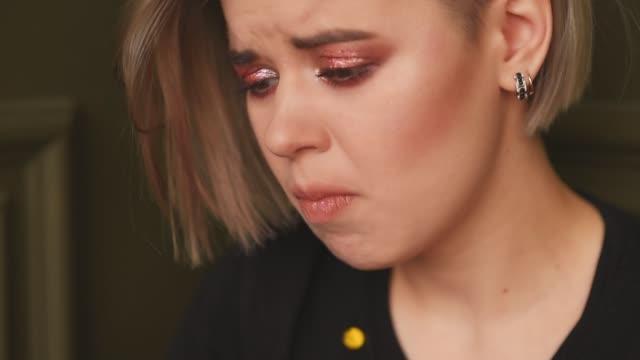 vídeos de stock, filmes e b-roll de uma garota infeliz está sentada no chão sofrendo e comendo casca de mandarim. filmando um clipe. - clip art