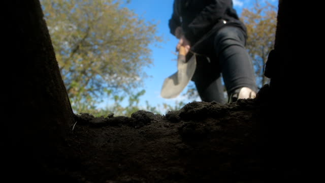 An unrecognizable person in dark clothes is digging a square pit against a blue sky with clouds. Point of view from the grave into which soil is sprinkled from a shovel.  Slow motion 200 fps