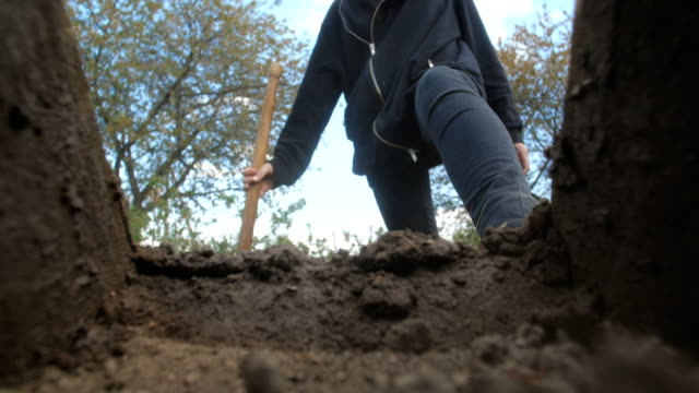 An unrecognizable person in dark clothes is digging a square pit against a blue sky with clouds. Point of view from the grave into which soil is sprinkled from a shovel.  Slow motion 50 fps 4k
