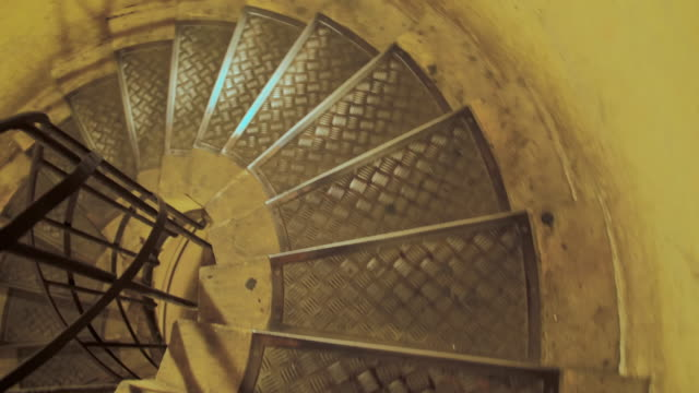An unrecognized person is going down the spiral staircase. Slow Motion. First-person view