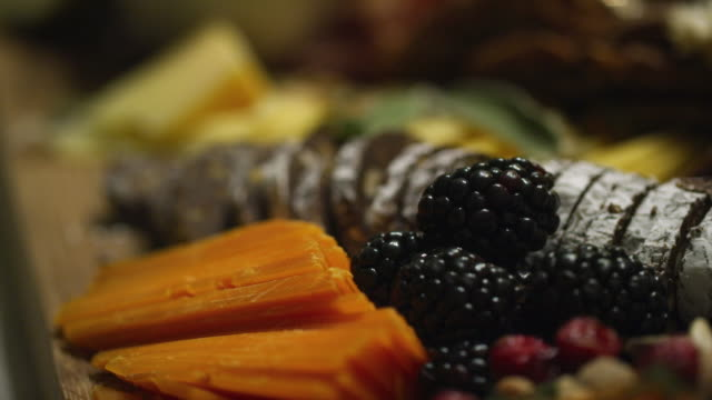 An Up-Close Shot of Cheeses, a Chocolate Log, and Blackberries on an Appetizer Charcuterie Cheeseboard at an Indoor Celebration/Party
