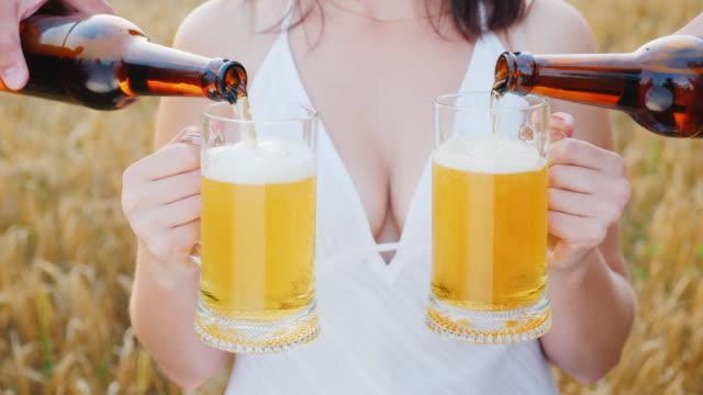 una donna trattiene due bicchieri di birra, su entrambi i lati viene versata una bevanda fresca - due oggetti video stock e b–roll