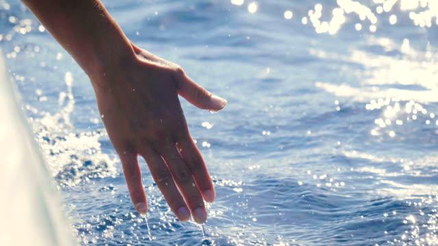 vídeos de stock, filmes e b-roll de um jovem mulherengo em um barco toca a água e desfruta do dia no mar ao lado das ondas do barco. - veículo aquático
