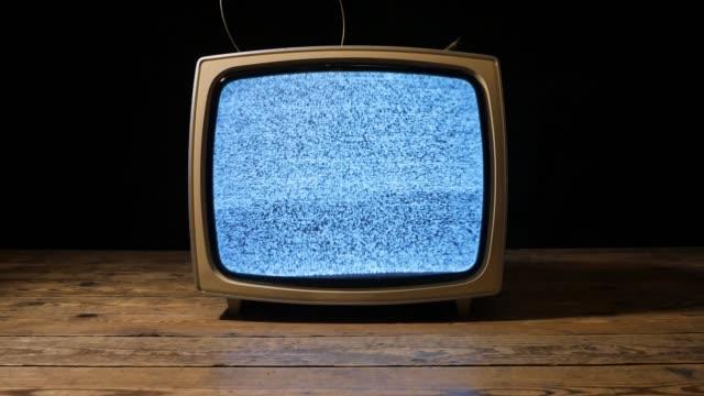 黒の背景の前に粒状のノイズとアナログヴィンテージテレビ - 木目のビデオ点の映像素材/bロール