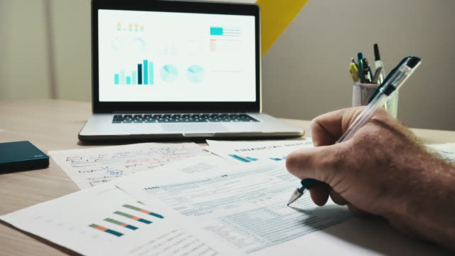 vídeos de stock e filmes b-roll de analyzing the stock markets and filling the 1040 tax form - benefits