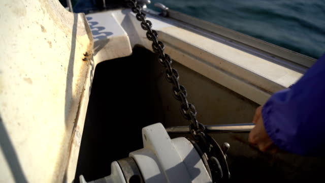 Anchor chain with a winch On a yacht, an anchor chain is lowered into the water with a winch towing stock videos & royalty-free footage