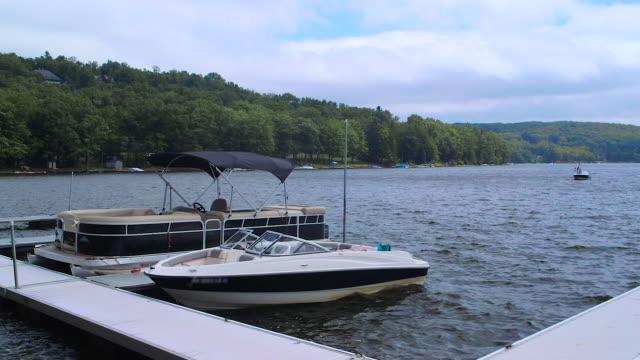 vídeos y material grabado en eventos de stock de barcos anclados cerca de dock bobbing en lake durante el día nublado del verano - amarrado