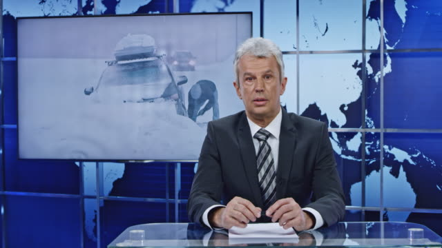 LD Anchorman presenting breaking news on a severe snowstorm Wide locked down shot of an anchorman presenting breaking news on a severe snowstorm striking the area and the footage is show on the screen behind him. Shot in Slovenia. journalist stock videos & royalty-free footage