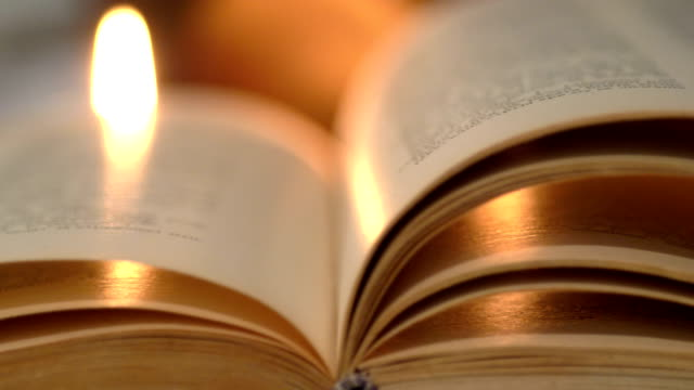 Ancient book lit by candles video