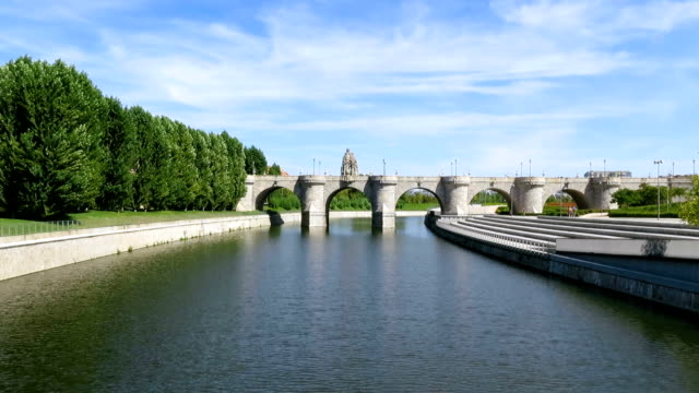 ancient bridge in Madrid river landmark of green water river Manzanares at garden park forest and ancient stone Toledo Bridge made in year 1718 in Madrid city Spain Europe hd format stock videos & royalty-free footage
