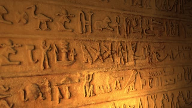 ancient egyptian lettering inside tomb of the pyramids lit by candle alt - египет стоковые видео и кадры b-roll