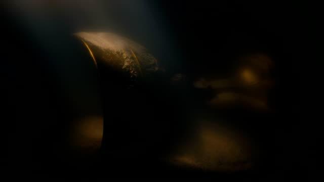 ancient gold cup treasure in sun rays underwater - scatola del tesoro video stock e b–roll