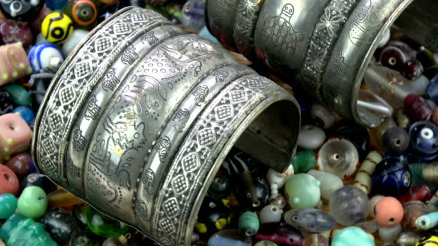 Ancient indian bracelet rotating on old beads background