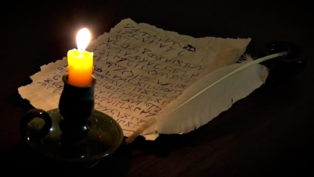 Ancient Manuscript and Burning Candle The manuscript was written with a quill pen in an unknown alphabet. Next to the candle holder lit candle paranormal stock videos & royalty-free footage