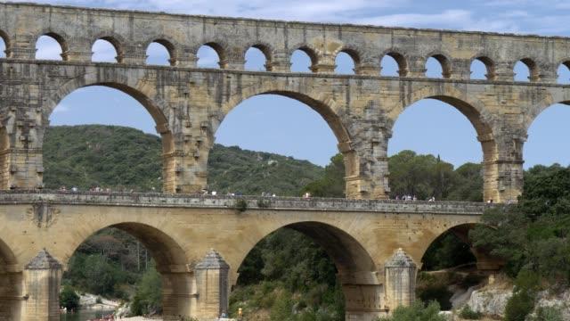 Ancient novel aqueduct Pont du Gard, butts the Gardon River. Towards Pont-du-Gard, France. Pannnig shot. 4K, UHD Ancient roman aqueduct Pont du Gard, crosses the Gardon River. Vers-Pont-du-Gard, France. Pannnig shot. 4K, UHD aqueduct stock videos & royalty-free footage