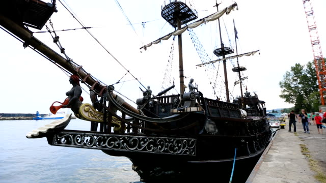 Ancient pirate ship moored in bay of Gdansk attracting tourists, sequence video