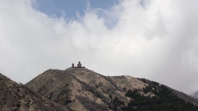Ancient temple of the Holy Trinity Gergeti in the mountains on a background of white clouds floating. Georgia, Caucasus.