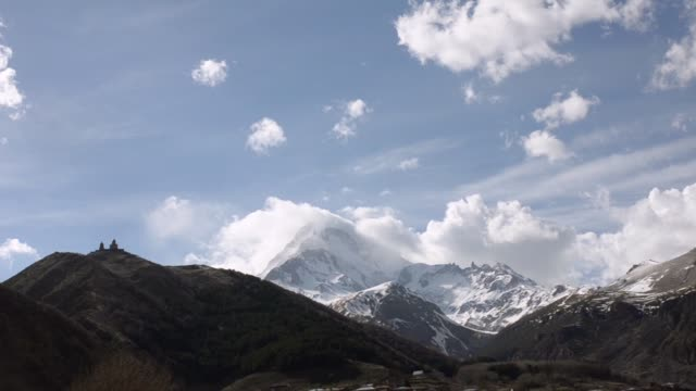 Ancient temple of the Holy Trinity Gergeti on a background of white clouds floating and Mount Kazbek. Georgia, Caucasus.