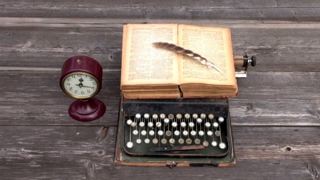 ancient typewriter and old book on wooden background video