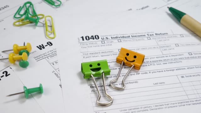 W-9 and 1040 Taxe Form with Smiles Binder Clips on Table