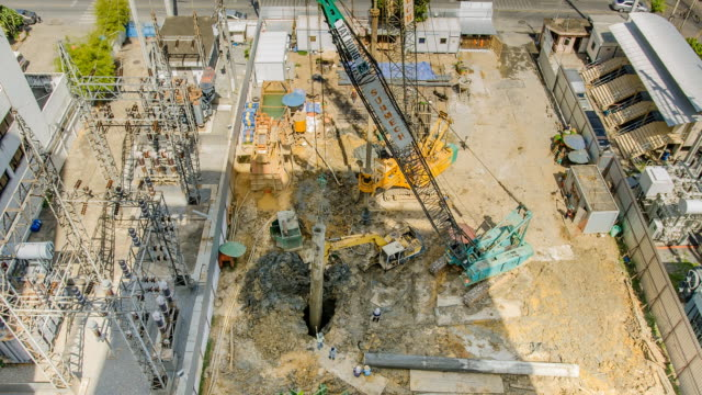 TL and aerial view: molding foundation pile TL and aerial view: molding foundation pile under construction Site. bulldozer is used to open soil. A big crane is used to move plastic molded foundation pile molding a shape stock videos & royalty-free footage