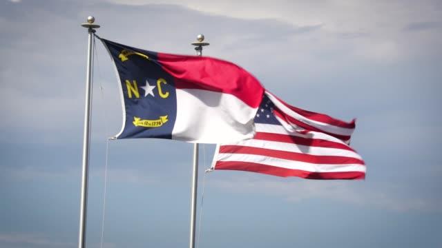 nc and american flags - asta oggetto creato dall'uomo video stock e b–roll